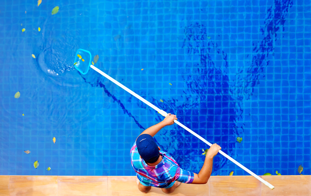 A professional pool cleaner is cleaning the pool